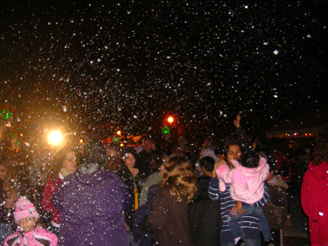 fake snow falls on a city event